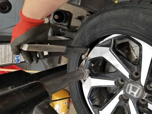 inserting the tire iron into the inner bead of the tire