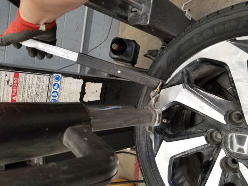 inserting the tire iron into the outer bead of the tire